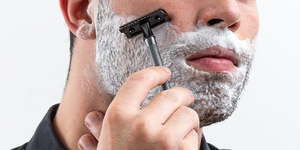 Mann mit eingeschäumten Bart rasiert sich mit schwarzem Rasierhobel der Marke Merkur